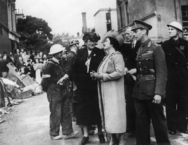 King George VI together with Queen Elizabeth chatting with Air Raid Patrol wardens and inspecting bomb damage in South West London during the Blitz, 1940