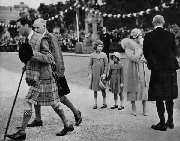 King George VI and Queen Elizabeth are received at Ballater, Scotland, before journeying onwards to Balmoral. Princess Elizabeth and Princess Margaret stand in the centre of the photograph.  1937