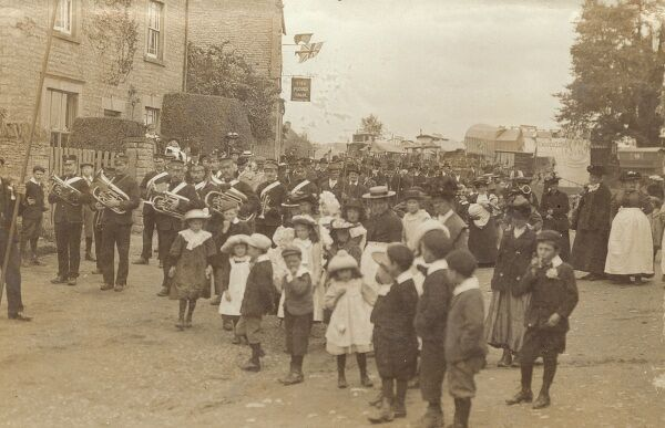 Kingham, Oxfordshire - Outside The Plough Inn. There appears to be a Fair in progress in the background and a procession is assembling to the left, with a brass band at it's head. Date: 1906
