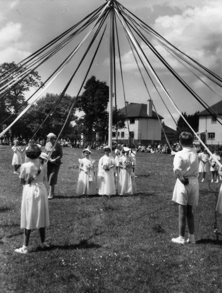 The May Queen and her Maids of Honour (and one boy!) by the Maypole, at the Ram Roasting Fair, Kingsteignton, Devon, England, held annually on Whitsun Monday. Date: 1950s