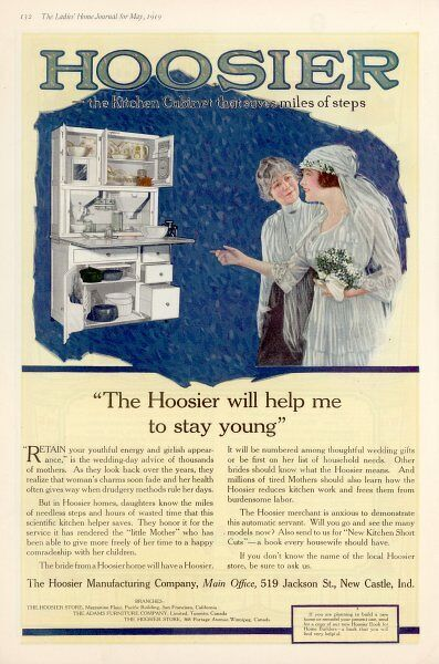 Still wearing her wedding dress, a bride admires the Hoosier Kitchen Cabinet which will help her to stay young because it will save her so much kitchen drudgery