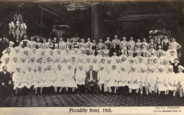 Group photo of kitchen staff and others, possibly with the manager at the centre of the front row, Piccadilly Hotel, London W1. Date: 1908