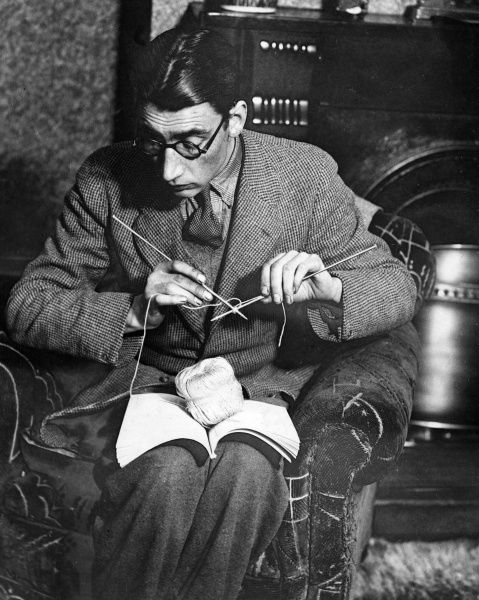 A bespectacled boffin attempts a spot of knitting, carefully following the knitting pattern! Date: 1930s