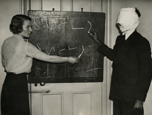 "Undated photograph of Kuda Bux and one of his experiments with ""eyeless sight"": with head bandaged, he is duplicating shorthand characters drawn on a blackboard by Lucie Kay. HPG/1/12/9 (v)&quot"