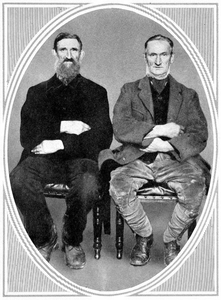 Photographic portrait of two agricultural workers, taken in 1913m but wearing clothes and sporting facial hair from an earlier era