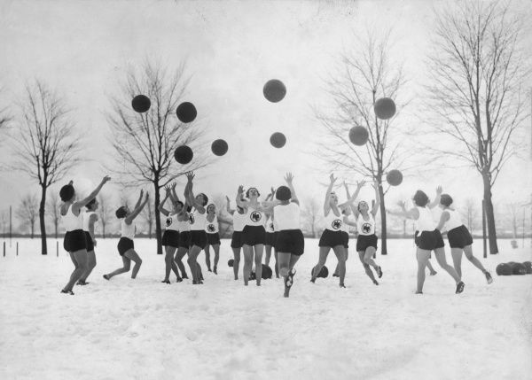 Female athletes exercise by throwing large balls into the air, whilst outdoors in winter snow