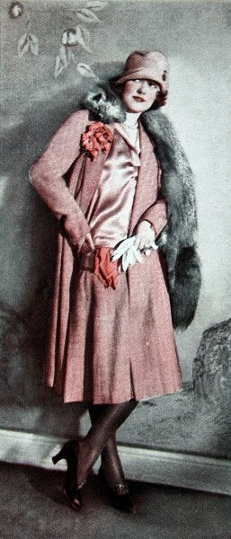 A suit featuring a long jacket made of Gabardine and Crepe de Chine. The outfit was accessorised with matching corsage and handkerchief and a sliver fox stole