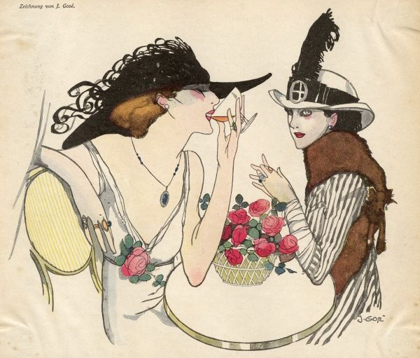 Two elegant woman drink at a table with flowers on it.  circa 1932