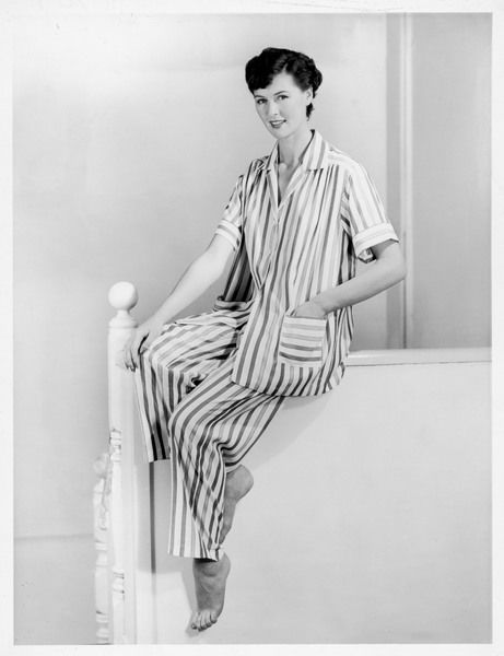 A young woman sitting on a newly d.i.y'ed boxed-in bannister wears a pair of short-sleeved pyjamas - a feminine version of the classic men's striped p.j's