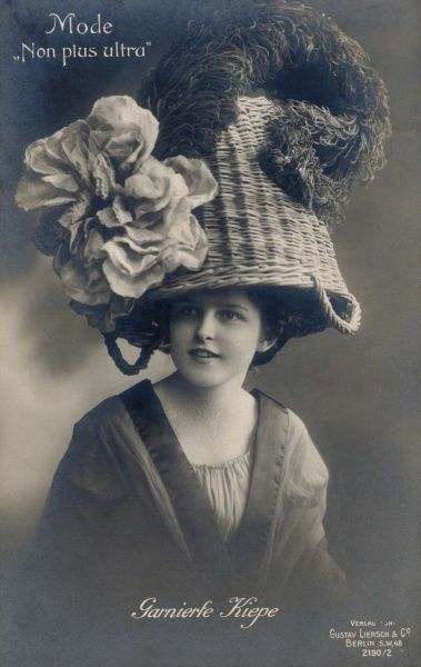 Lady in a basket hat with an ostrich plume and cloth flower. Date: 1920s