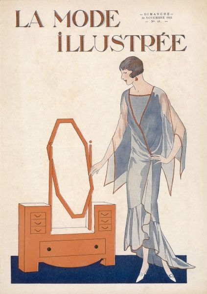 An elegant lady in a blue evening dress stands by her art deco dressing table