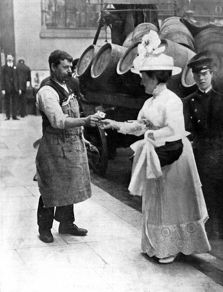 Photograph showing the Lady Mayoress of London selling a wild rose to a drayman on Alexandra Rose Day, 1912