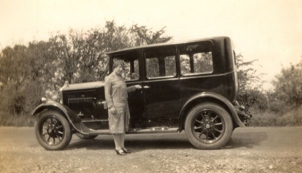 A well-dressed middle aged lady standing alongside a medium-size family car, viewed in profile