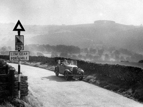 Female motorists enjoying a drive in the British countryside. Note the steep hill '1 in 7' sign. Date: 1930