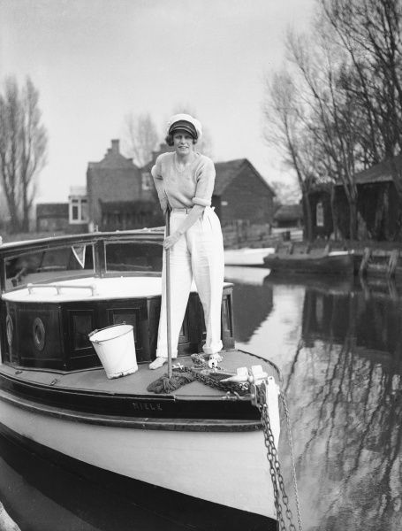 A stylish young woman mops the deck of her boat, moored on the banks of the River Stour, England, getting it ready for a spot of Easter sailing!