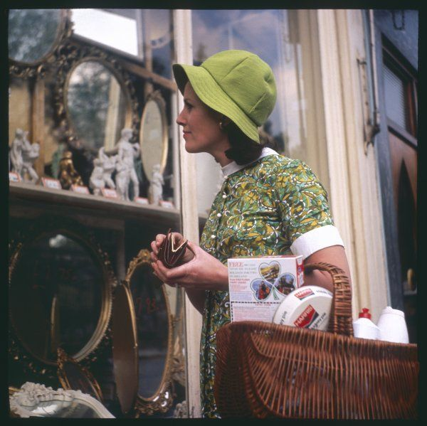 A woman in a green floppy hat and green dress browses in a shop selling various mirrors and ornaments. She holds a rather full wicker basket full of shopping over her arm