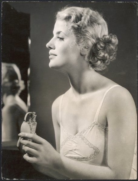 A lady in her slip, putting on her perfume before dressing