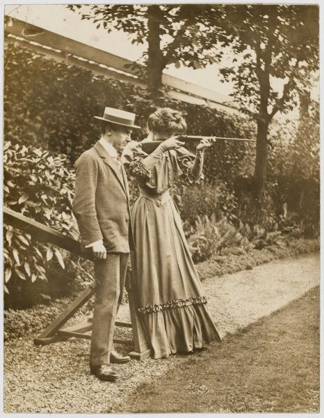 An Edwardian lady learns to shoot an air rifle with the help of a man in suit and boater