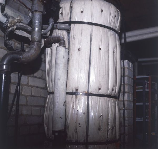 A lagged hot water boiler in a household basement or loft. Date: 1970s