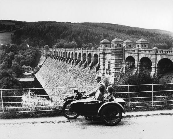 A young couple take in the magificient Lake Vyrnwy Dam, Powys Wales, from their motorcycle and sidecar. The lake was created when the dam was built 1881 - 1888