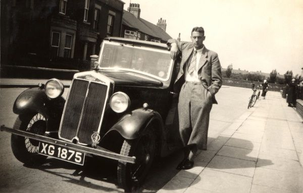 A Lanchester car (10 HP) and suave-looking driver in relaxed pose on a suburban street