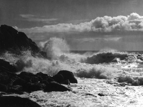 A dramatic study of waves crashing against the rugged coastline, clouds looming above, Land's End, Cornwall, England. Date: 1950s
