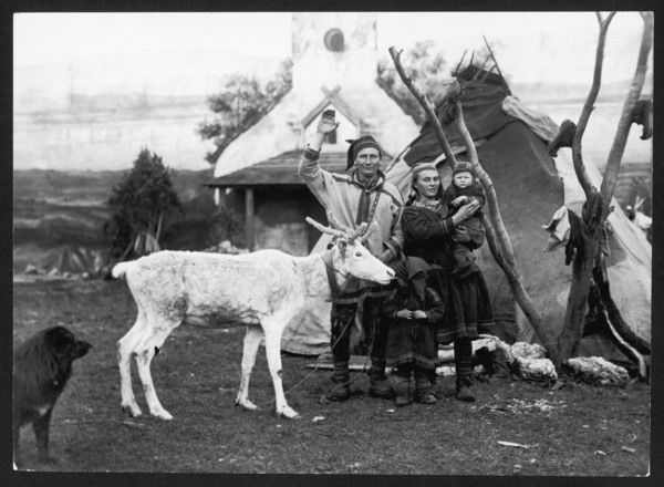 A Lapland man and woman with their two children, reindeer and dog, outside their tepee