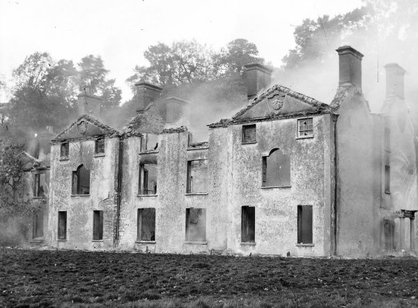 A large country house gutted by fire, probably in the Mid Wales area. The fire is recent, as smoke is still drifting from the building. Two of the upstairs windows are bricked up, so perhaps the house was empty when the fire started