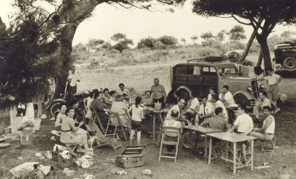A large Genoese extended family group take the car into the hills for a summer picnic. Date: 1930s