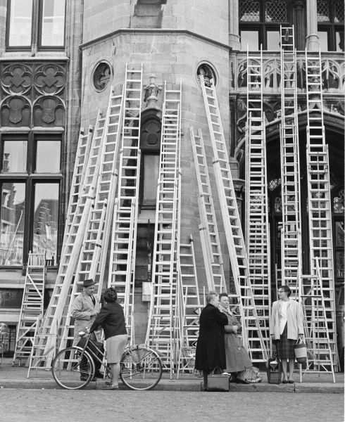 A large number of ladders on display, leaning against a building