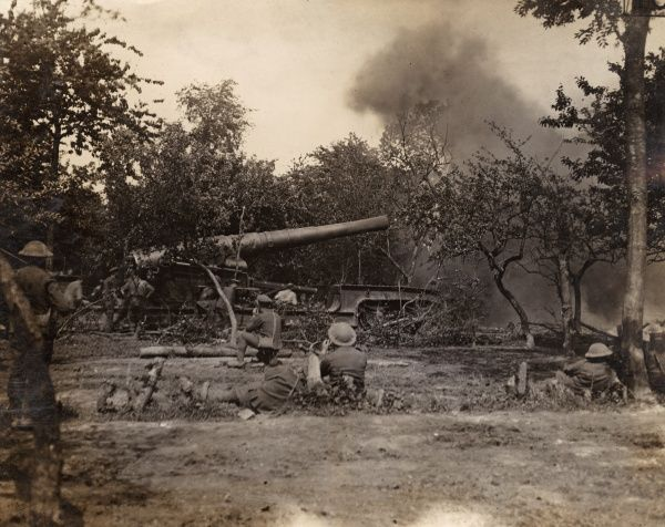 A large railway mounted gun firing from tree cover during the First World War. Date: 1914-1918