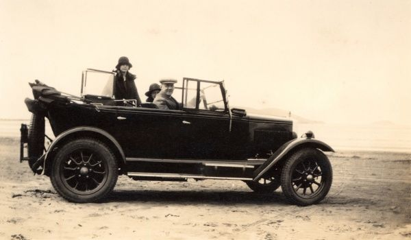 A large open-top saloon car on the beach