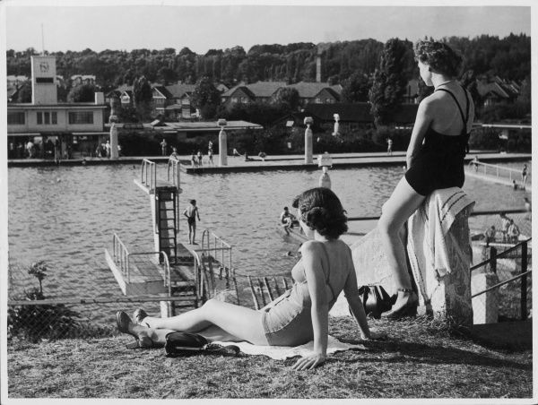 Two glamorous girls in bathing costumes and high heels surveying the scene at Larkswood open air swimming pool, Chingford, Essex