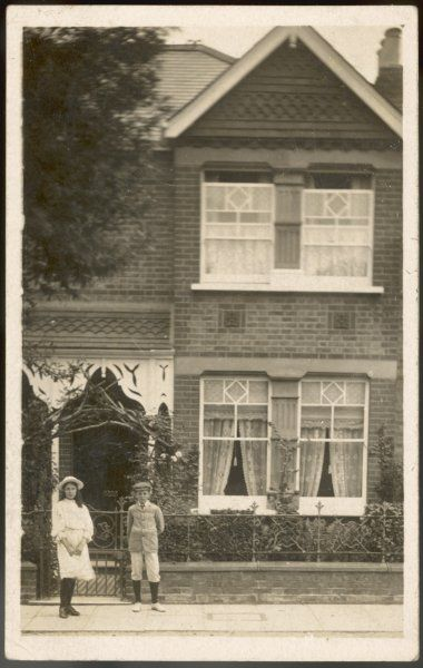 A typical suburban semi- detached home : the children of the house stand outside the gate