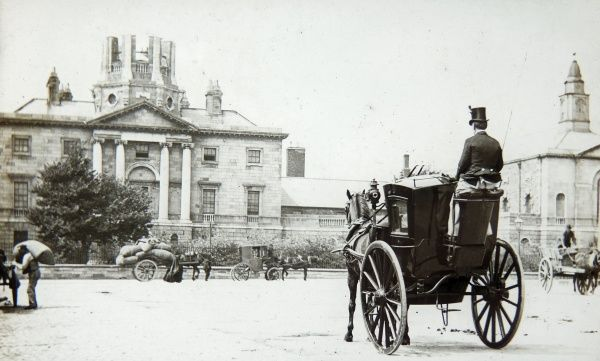 A late Victorian street scene with a horse-drawn carriage in the foreground, and various other horse-drawn vehicles in the distance