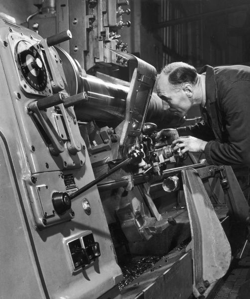 A metalworker checks the settings on a large industrial lathe. A lathe is a machine tool which spins a block of material to perform various operations such as cutting, sanding, knurling, drilling, or deformation, to create a spherical object of varying widths