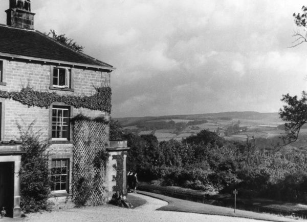 Three young men in shorts take in the magificent scenery at Leam Hall Youth Hostel, near Grindleford, Derbyshire, England, with its fine view of the Upper Derwent Valley. Date: 1930s