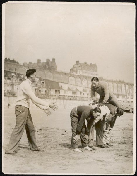 Five men playing leap frog on the sandy beach at Ramsgate. Kent, England
