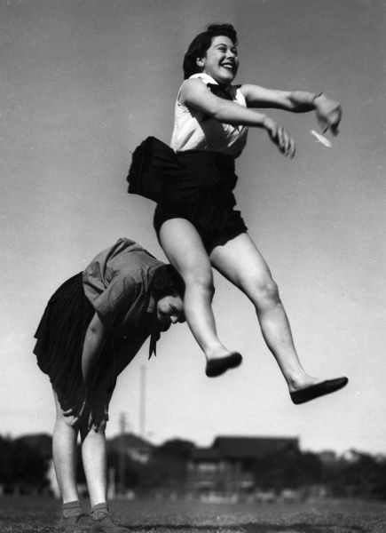 Two Australian girls playing leapfrog. Under an Australian National Health scheme, children from deprived areas were taught how to enjoy exercise and stay healthy. Date: 1940s