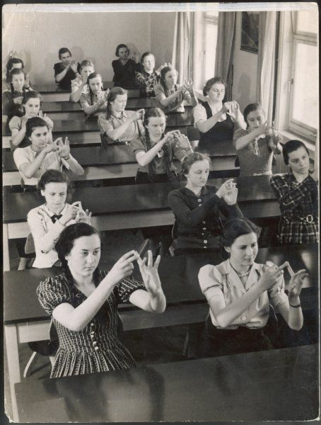 A class of young women learning sign language at a school for the deaf