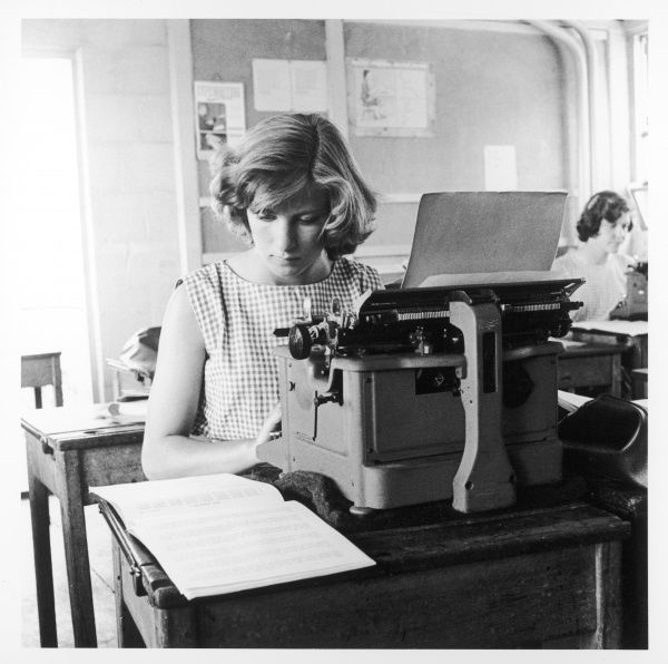 A young woman learns to type at a secretarial school, on a massive manual machine