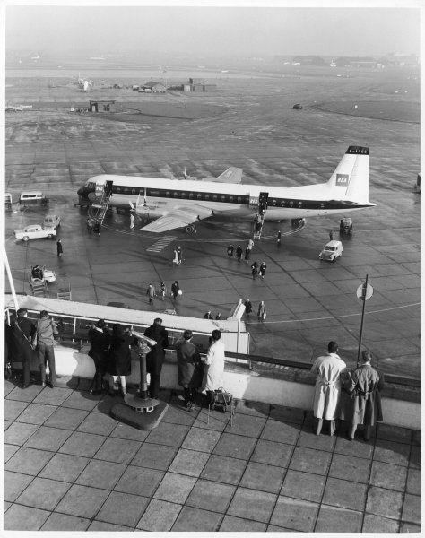 Passengers alighting from a BEA Bristol Britannia aeroplane, watched by friends and relatives