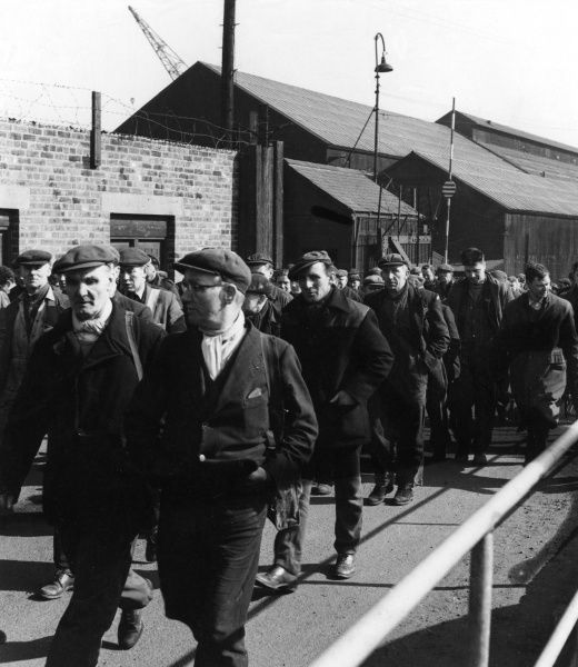 Shipyard workers coming off their shift. Date: 1950s