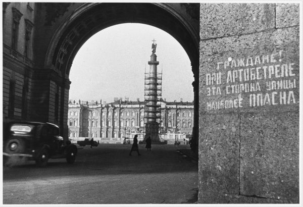 The sign reads 'Citizens! During artillery fire, this is the most dangerous side of the street'. Palace Square and the Winter Palace are in the background