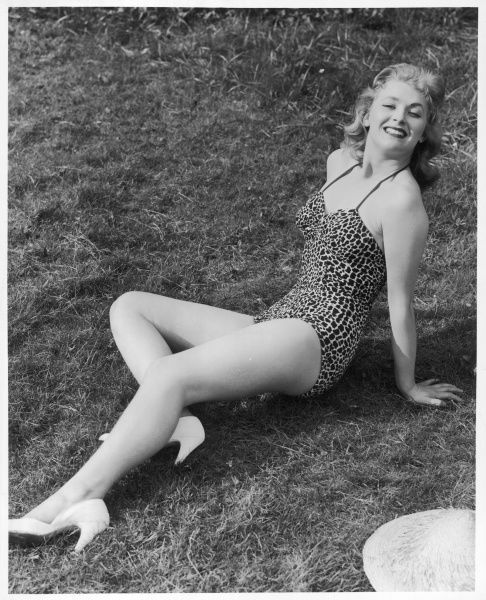 Blonde 'pin-up' model reclines on the grass in an ocelot / leopard print bathing costume, a coolie hat on the ground beside her, and white stilettos on her feet
