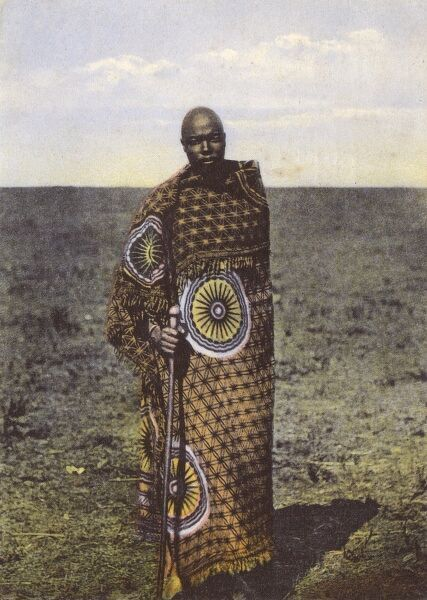 Basutoland (now Lesotho) Policeman 'with blanket' - seemingly refering to his wonderful fabric wrapped cloak of a superb printed material. Date: 1909
