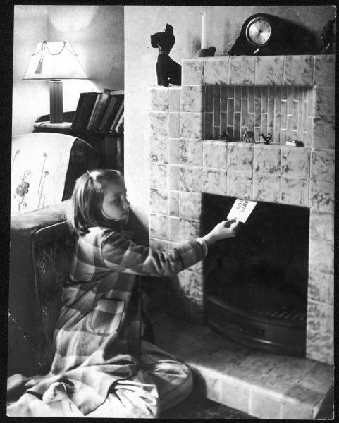 A little girl in her dressing gown, leaves a note up the chimney for Santa Claus on Christmas Eve