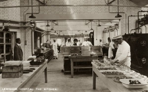 Uniformed catering staff prepare meals in the kitchens of Lewisham Hospital in south east London. A cook at the right is making up plates of salad. Large metal boxes carry the names of hospital wards