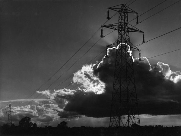 'Power and light', a study of electricity sub power lines and pylons among the clouds. Date: 1960s
