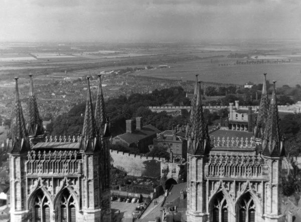 A fine view, looking westwards, from the main tower of Lincoln Cathedral, with the tops of its twin towers and the Castle Gateway below, Lincolnshire, England. Date: 1950s